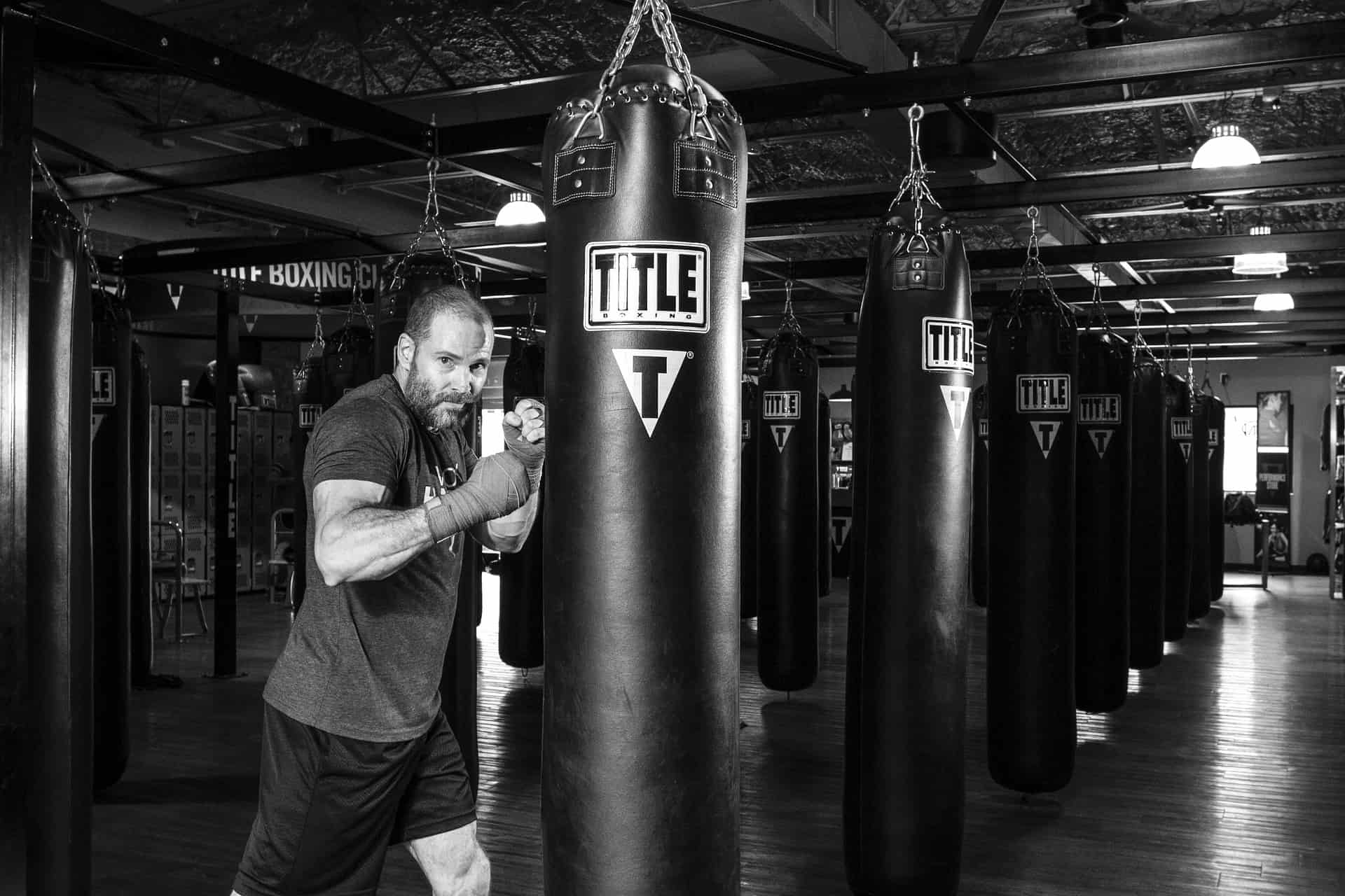 A man is practicing with boxing sandbag