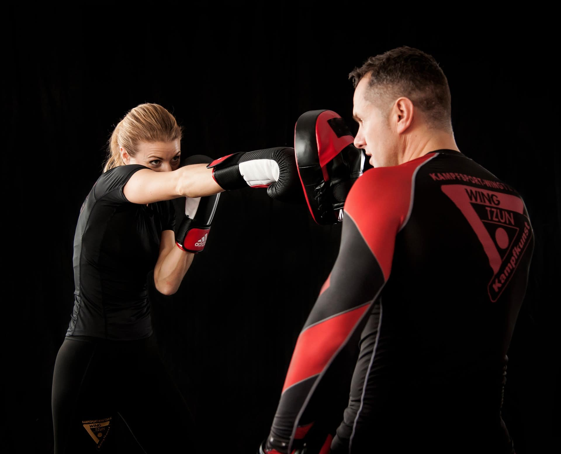 a woman is throwing a punch to her trainer