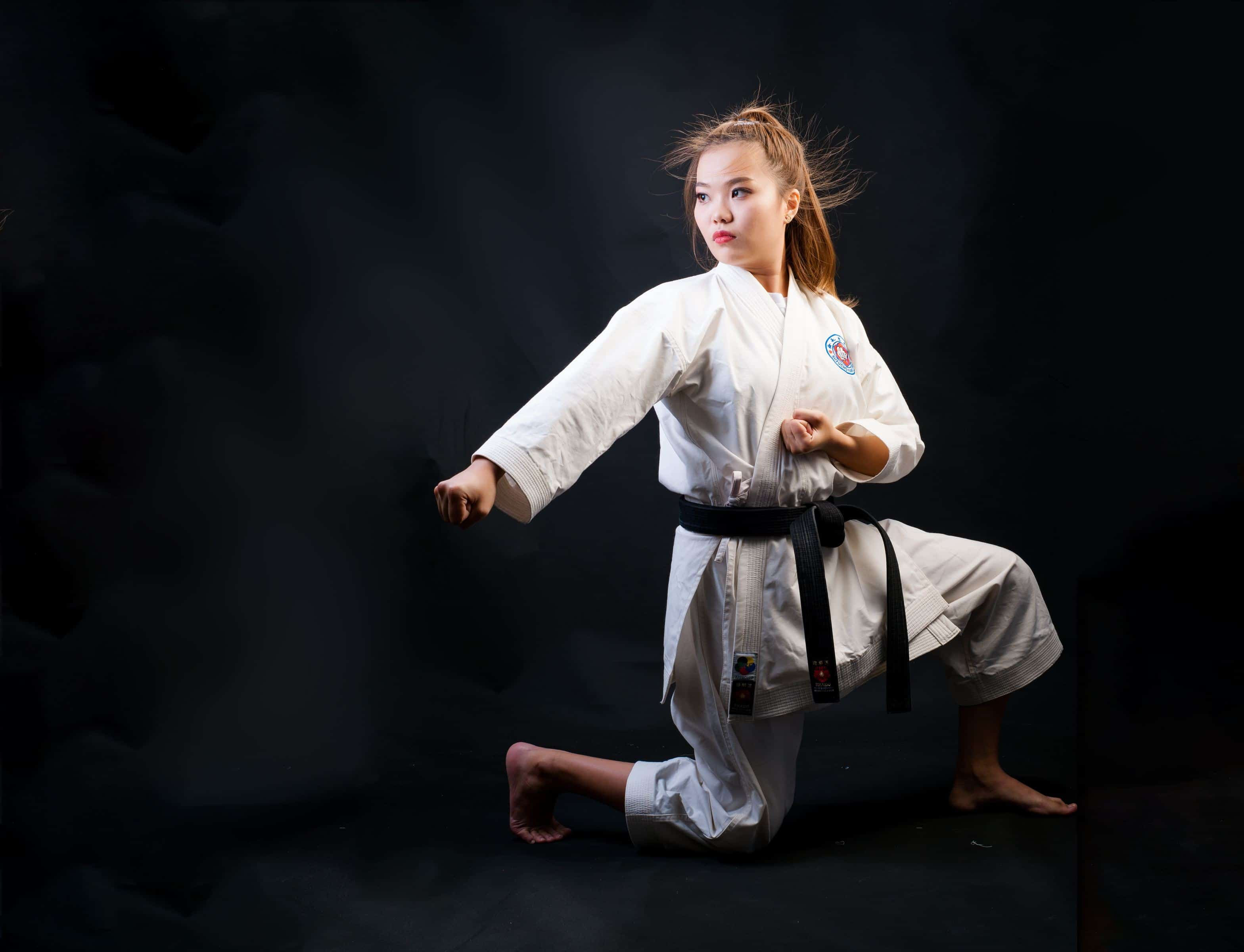a woman is doing a kungfu move