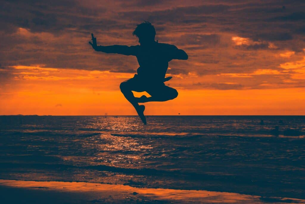a person is doing a karate-jump pose at the beach
