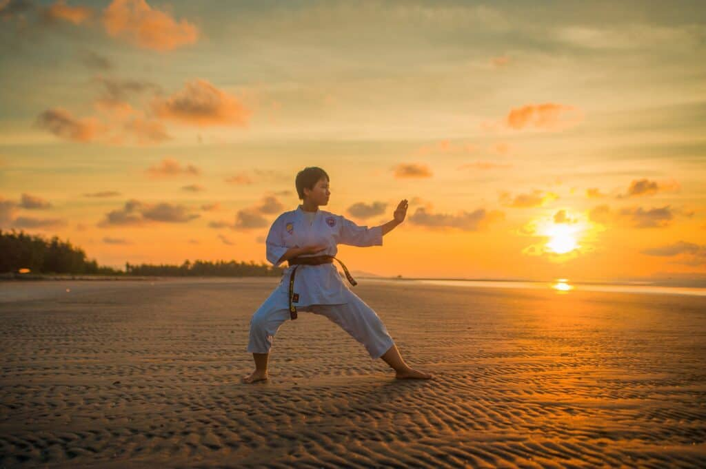 a boy is practicing martial art at the beach