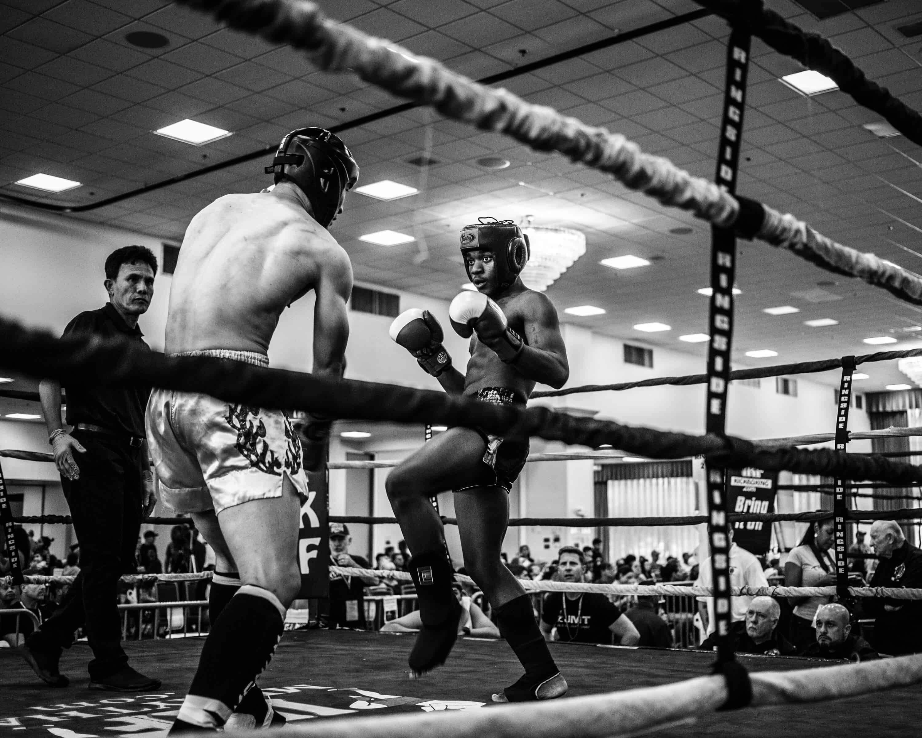 a black and white photo of two men do a boxing sports in a boxing ring